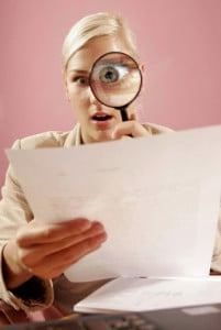 work environment- woman with a magnifying glass over some paperwork in modern office-on pink